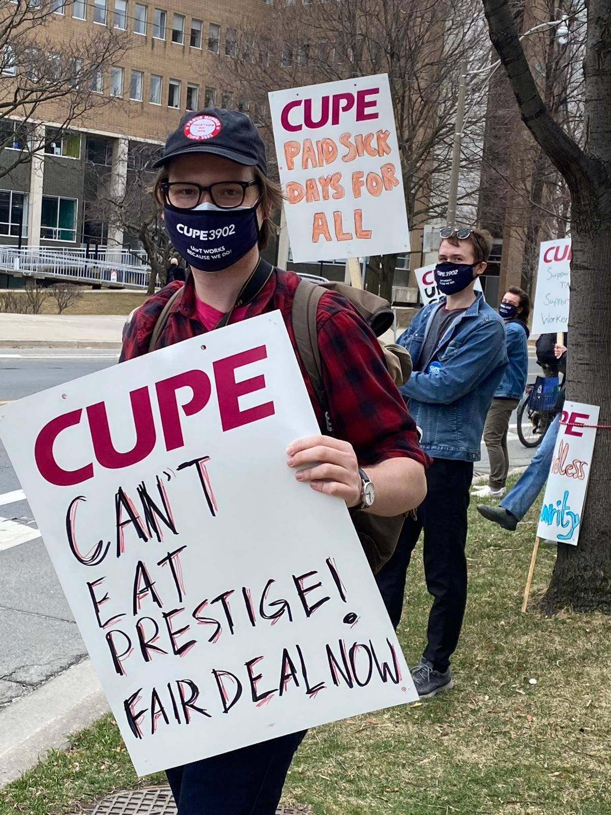 """Eriks Bredovskis, holding a strike sign that says """"CAN'T EAT PRESTIGE! FAIR DEAL NOW"""""""